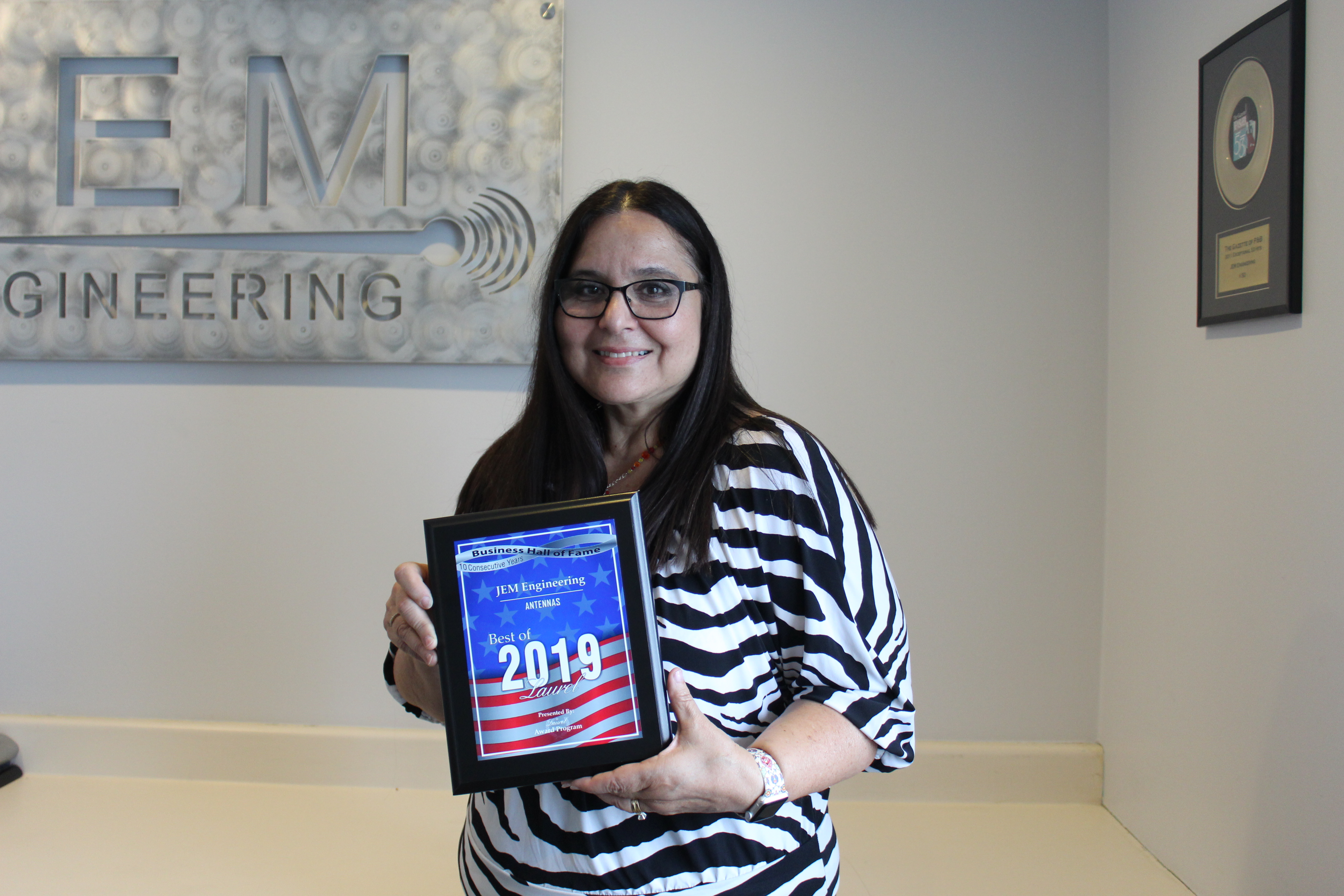 Nancy Lilly, CEO of JEM Engineering, holding The 2019 Best of Laurel Award